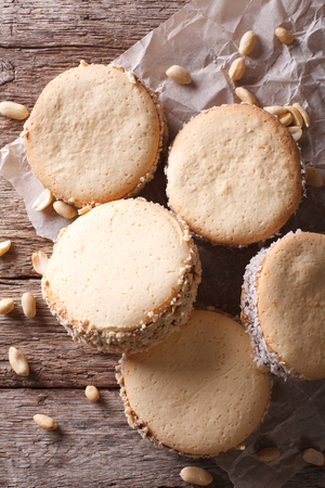 alfajores: Tasty cookies with cream on paper close-up on the table. vertical top view Stock Photo
