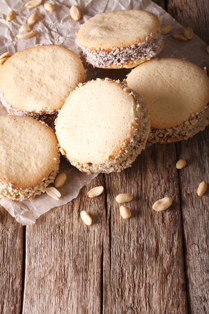 alfajores: Argentine cuisine: alfajores with cream on paper close-up on the table. vertical Stock Photo