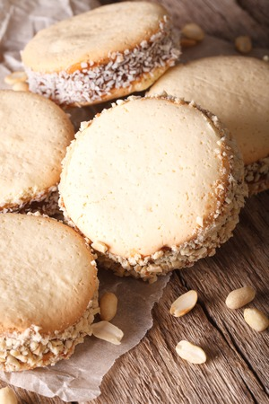 alfajores: Delicious Alfajores cookies on paper close-up on the table. Vertical, rustic