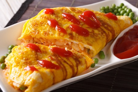 Japanese omelet with rice and ketchup Omurice close-up on a plate. horizontal