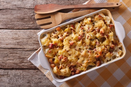 French cuisine: tartiflette potatoes with bacon and cheese close up in baking dish. horizontal top view Stock fotó