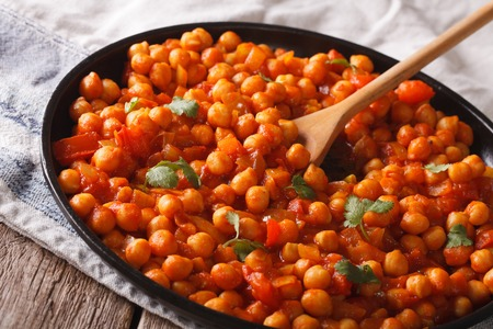 chaat: Indian Cuisine: chickpeas in tomato sauce with spices close-up on the table. Horizontal