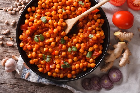 chaat: Delicious Indian cuisine: Chana masala with ingredients close-up on the table. horizontal top view Stock Photo