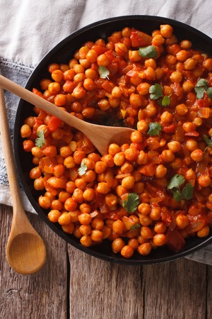 chaat: Indian Food: chickpeas in curry sauce on a table close-up. Vertical top view