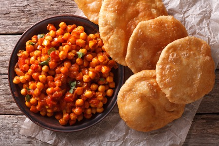 chaat: Delicious Indian Chana masala and puri bread close-up on the table. Horizontal top view
