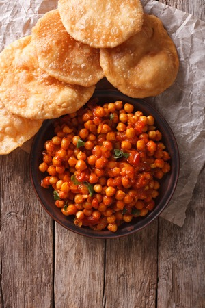 chaat: Delicious Indian Chana masala and puri bread on the table. Vertical top view