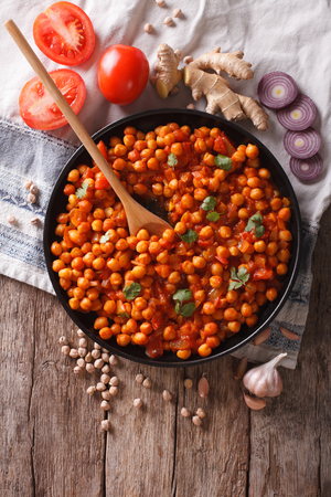 chaat: Delicious Indian cuisine: Chana masala with ingredients on the table. Vertical top view