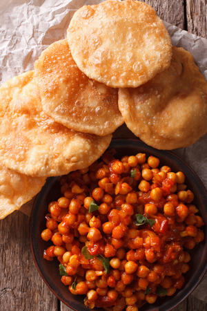 chaat: Indian Chana masala and puri bread close-up on the table. Vertical top view