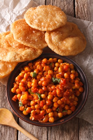 chaat: Indian Chana masala and puri bread close-up on the table. Vertical Stock Photo