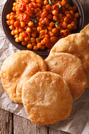 chaat: Indian bread puri and chana masala close-up on the table. vertical top view
