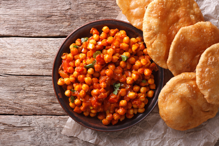 chaat: Delicious Indian Chana masala and puri bread on the table. Horizontal top view