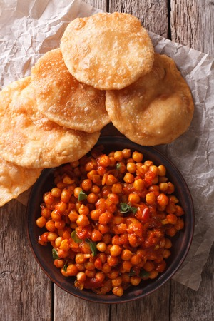 chaat: Delicious Indian Chana masala and puri bread close-up on the table. Vertical top view