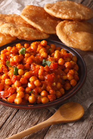 chaat: Indian Cuisine: Chana masala and puri bread close-up on the table. Vertical Stock Photo