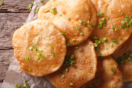 pani: Indian puri bread close-up on a paper on the table.  Horizontal top view Stock Photo