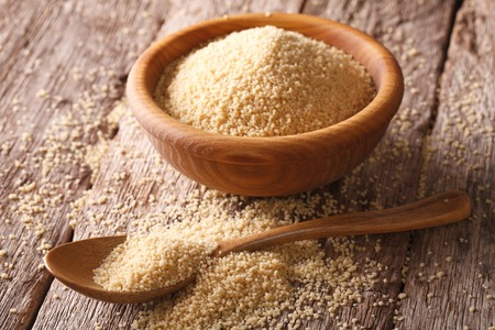 durum wheat semolina: Rustic couscous in a wooden bowl on the table close-up. Horizontal