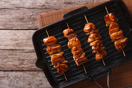 Japanese yakitori skewers of chicken on a grill pan. Horizontal top view