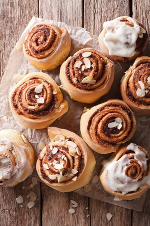 Cinnamon rolls with almond close up on the table. vertical top view