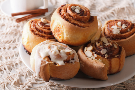 cinnamon swirl: Freshly baked cinnamon rolls with almond close up on a plate and coffee. horizontal
