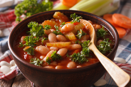 Bean soup with vegetables and ingredients macro on the table. horizontal
