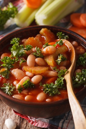 Bean soup with tomatoes and celery close-up on the table. vertical Archivio Fotografico