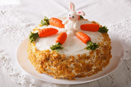 zanahorias: pastel de zanahoria con el conejito de dulces en primer plano en un plato sobre la mesa. horizontal