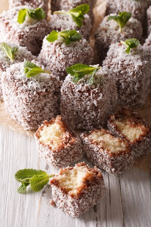 lamington: Sponge cake decorated with coconut close-up on the table. vertical, rustic style Stock Photo