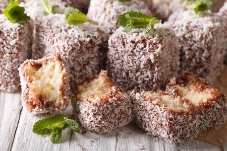 lamington: Australian Lamington cake with coconut macro on the table. Horizontal Stock Photo
