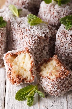 tucker: Australian Lamington cake with coconut macro on the table. vertical