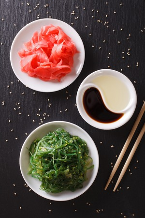 Japanese wakame seaweed salad with sesame seeds on a table. vertical top view