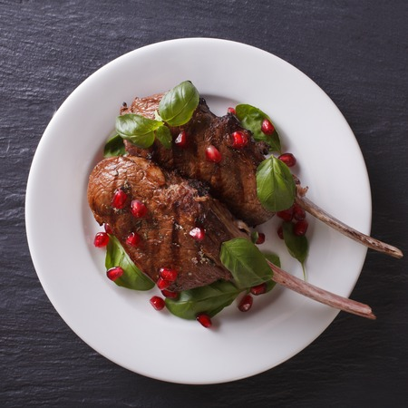 costilla: Grilled beef steak with pomegranate and basil close-up on a plate on the table. view from above Foto de archivo