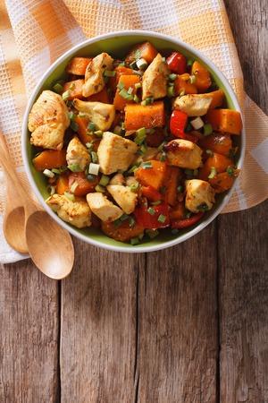 verticales: pollo al curry con calabaza y pimienta sobre la mesa. vertical vista desde arriba