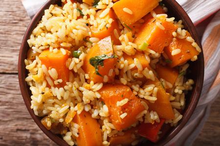 plato de comida: comida vegetariana: arroz con calabaza en un tazón de primer plano sobre la mesa. Vista horizontal desde arriba
