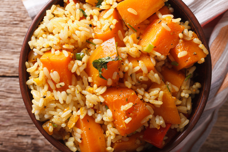 Vegetarian food: rice with pumpkin in a bowl close-up on the table. Horizontal view from above