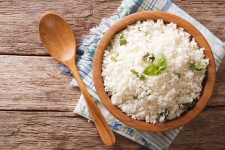 バジル風味カリフラワーご飯はテーブルの上にボウルのクローズ アップ。水平トップ ビュー 写真素材