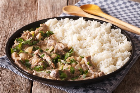 beef stroganoff: Russian cuisine: beef stroganoff with rice close-up on a plate on the table. horizontal