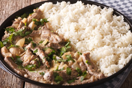 beef stroganoff: beef stroganoff with mushrooms and rice close-up on a plate on the table. horizontal