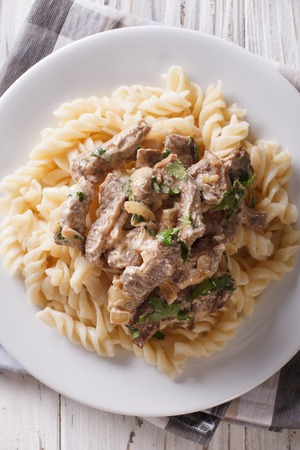 beef stroganoff: Delicious beef stroganoff with pasta fusilli close-up on a plate on the table. Vertical view from above Stock Photo