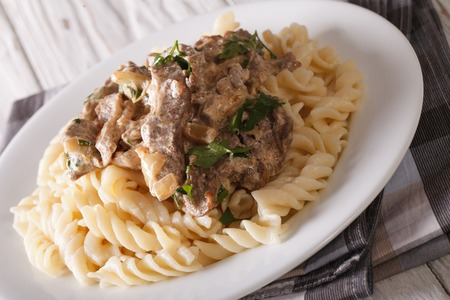beef stroganoff: Delicious lunch: beef stroganoff with pasta close-up on a plate on the table. horizontal Stock Photo