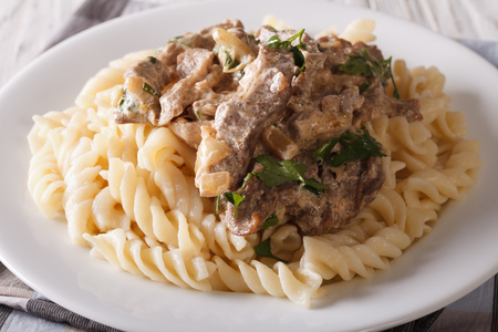 beef stroganoff: beef stroganoff with pasta fusilli closeup on a plate on the table. Horizontal Stock Photo