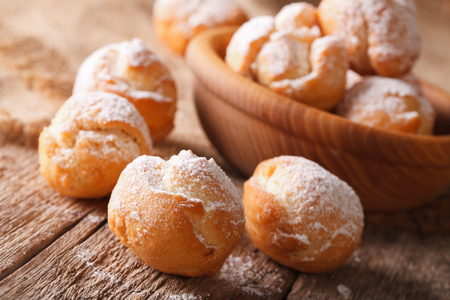 zeppole: Italian Castagnole with powdered sugar in a bowl close-up on the table. horizontal