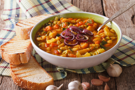 Tuscan ribollita thick soup with bread close up in a bowl on the table. horizontal