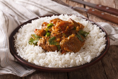 Traditionele rundvlees Madras met garnituur basmati rijst close-up op een bord op de tafel. horizontaal