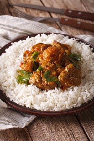 rice plate: Indian cuisine: beef madras with basmati rice close-up on a plate on the table. vertical