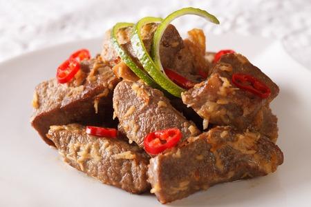 インドネシア料理: ビーフ ルンダン クローズ アップ皿の上。水平方向