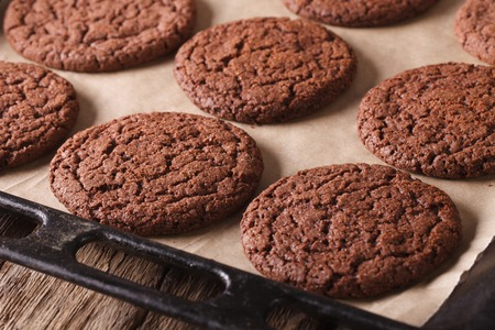 sweet sugar snap: Freshly baked chocolate cookies on a baking sheet on a table close-up. Horizontal Stock Photo