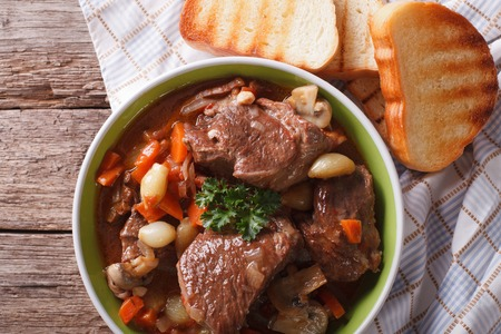 braised mushrooms: Rustic Beef Bourguignon in a bowl on a table close-up. Horizontal view from above