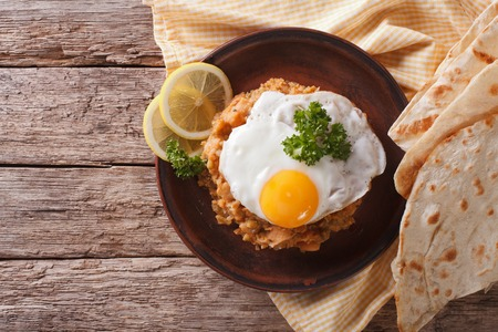 Egyptian breakfast: ful medames with a fried egg and bread on the table. Horizontal view from above