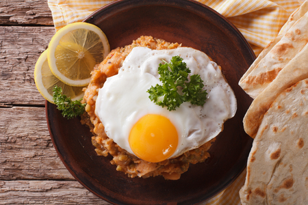 ful: Egyptian breakfast: ful medames with a fried egg and bread close-up on the table. horizontal view from above Stock Photo