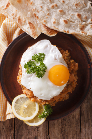 ful: Egyptian breakfast: ful medames with a fried egg and bread close-up on the table. vertical view from above Stock Photo
