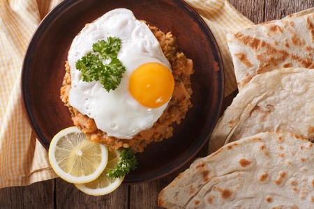ful: ful medames with a fried egg and bread close-up on the table. Horizontal view from above